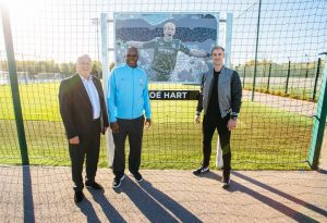 Mike Summerbee and Alex Williams with Joe Hart and his mosaic at the City Football Academy