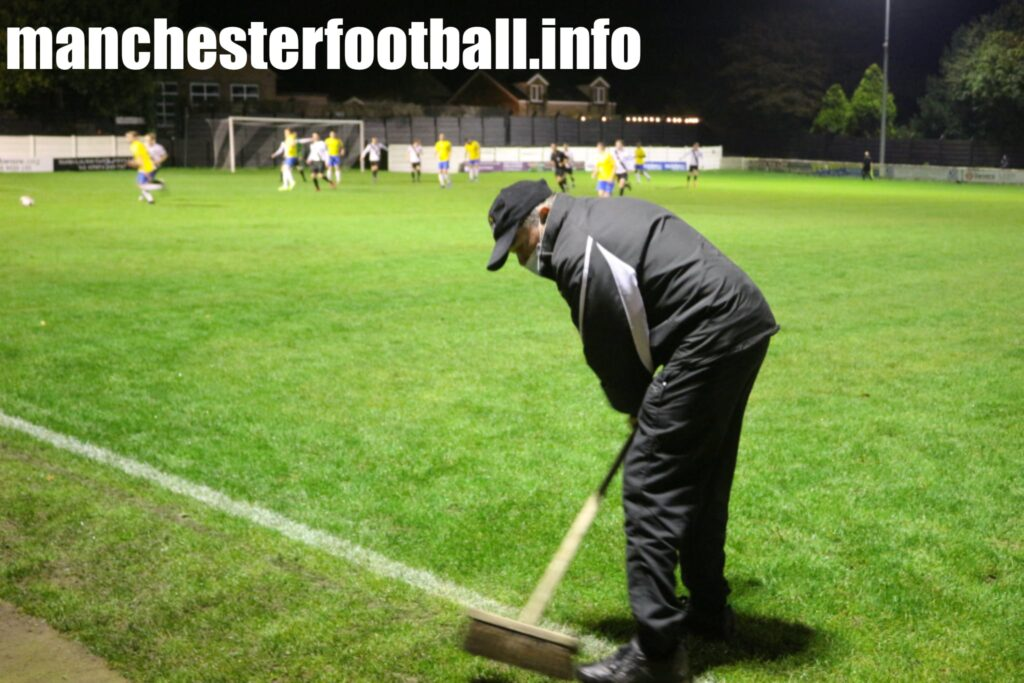 Mossley club official Steve Tague sweeping glass from the pitch after a floodlight bulb exploded