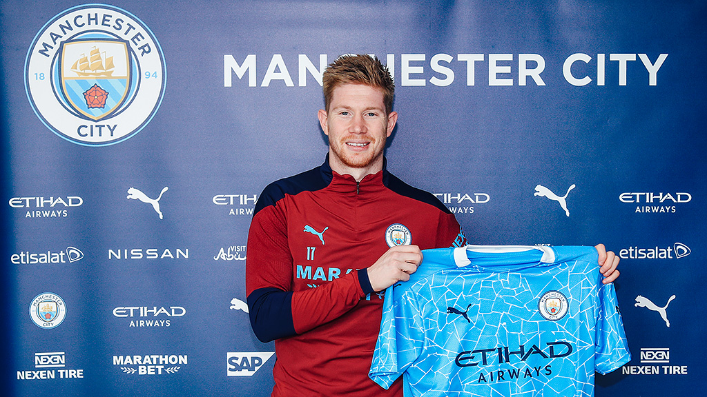 Kevin De Bruyne holds up a Man City shirt after signing a contract extension to stay at the club until 2025